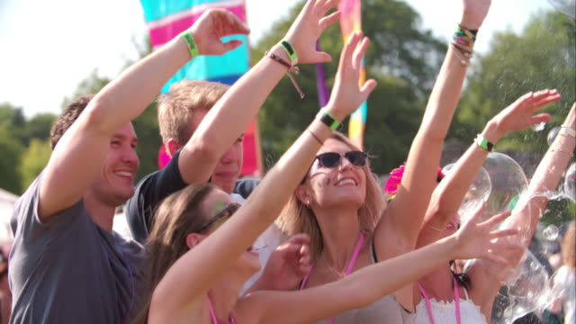 Friends enjoying bubbles at a music festival, slow motion video
