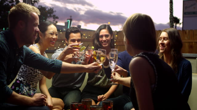 Friends Enjoying Night Out At Rooftop Bar Shot On R3D Friends Enjoying Night Out At Rooftop Bar Shot On R3D celebratory toast stock videos & royalty-free footage