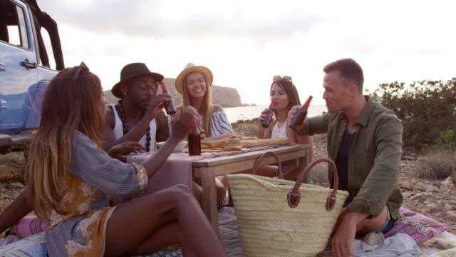vídeos de stock e filmes b-roll de friends enjoying picnic on cliffs by sea shot on r3d - ibiza