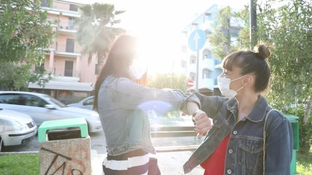 Friends finally meet again in the streets, holding hand wearing protective gloves - video