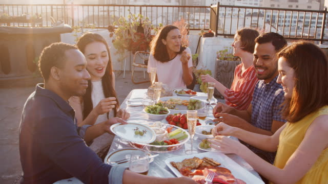 friends gathered on rooftop terrace for meal with city skyline in background - terrazza video stock e b–roll