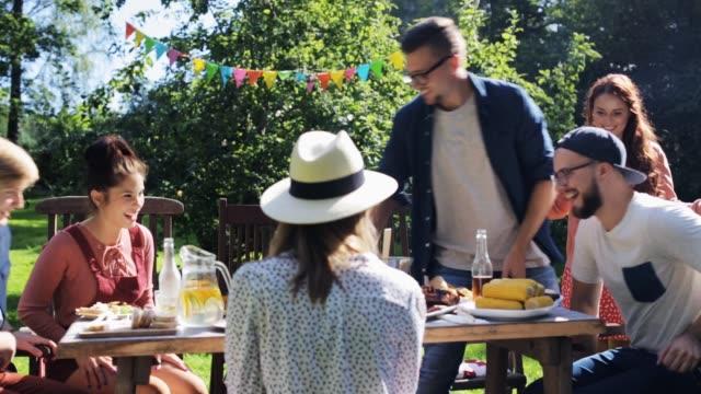 friends gathering for dinner at summer garden
