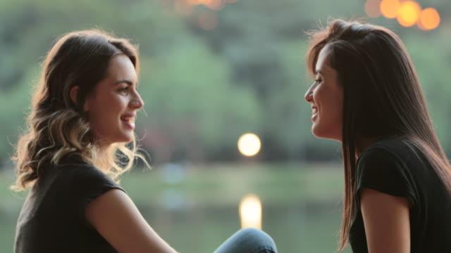 친구들이 공원 호수에서 햇빛 아래에서 야외에서 대화를 나누며 아이디어를 교환합니다. - 2명 스톡 비디오 및 b-롤 화면