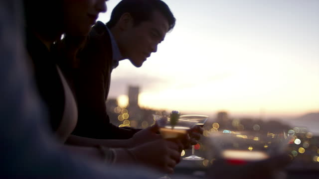 Friends hang out and drink cocktails on a rooftop bar at sunset in San Francisco video
