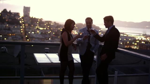 vidéos et rushes de amis se détendre et boire des cocktails sur le toit au coucher du soleil, avec en toile de fond de san francisco - man drinking terrace