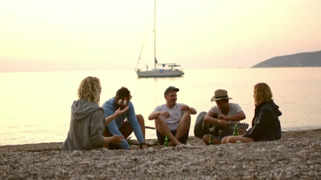 Friends hanging out, drinking beer and juggling stones on sunset beach, slow motion Friends hanging out, drinking beer and juggling stones on sunset beach. MS, slow motion.Shoot in 8K resolution 30 39 years stock videos & royalty-free footage