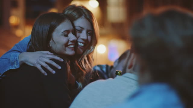 Friends hanging out A group of students hanging out in the city at night. They drinking beer and enjoying their gathering.   party social event stock videos & royalty-free footage