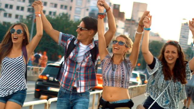 friends happily walking in the street, slow motion. - fianco a fianco video stock e b–roll