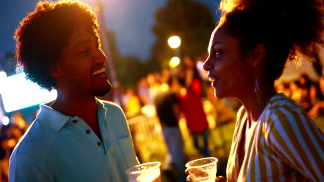 Friends having a casual talk. Closeup side view of two african american people having a casual conversation at a concert date. Blurry people and stage in background. low lighting stock videos & royalty-free footage