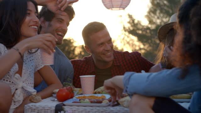 Amigos tener un picnic al lado de la caravana hablando juntos - vídeo
