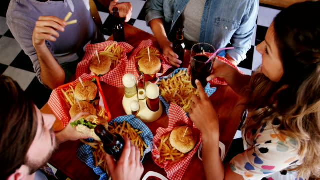 freunde, die burger und getränke im restaurant - schnellkost stock-videos und b-roll-filmmaterial