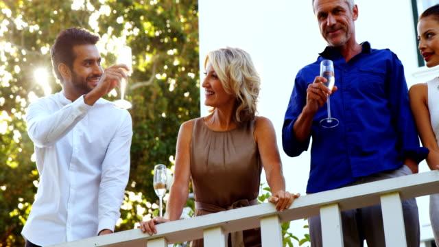 vídeos de stock e filmes b-roll de friends having champagne in balcony - enjoying wealthy life