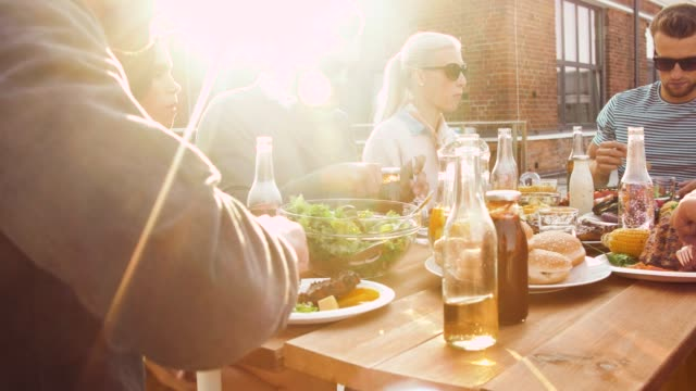 friends having dinner or bbq party on rooftop leisure and people concept - happy friends having dinner or bbq party and eating on rooftop in summer barbecue meal stock videos & royalty-free footage
