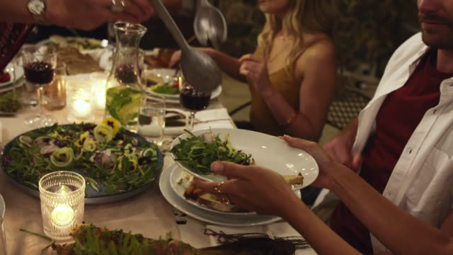 Friends having feast Woman serving food to friends at party. Group of friends having a dinner party. thanksgiving stock videos & royalty-free footage