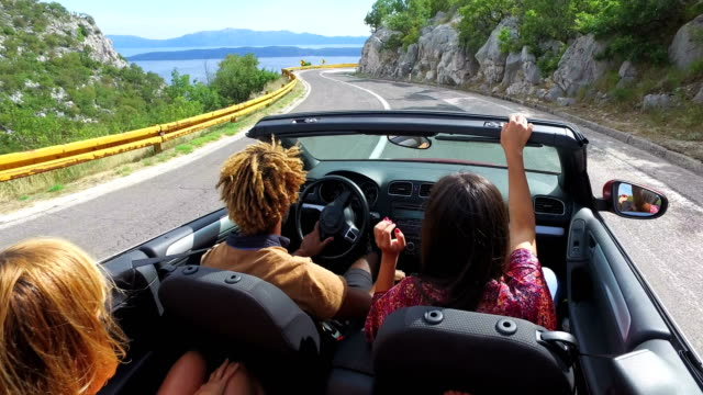 friends having fun driving on the road along the coast in red convertible - road trip стоковые видео и кадры b-roll