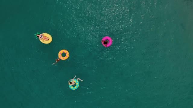 stockvideo's en b-roll-footage met vrienden plezier op floaties in water - opblaasband