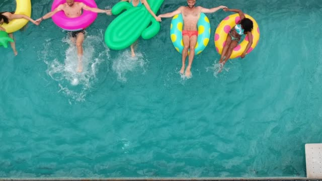 Friends having fun on inflatable rings in the pool