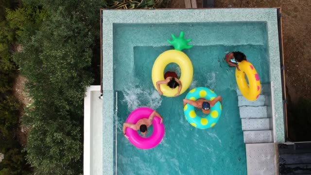 stockvideo's en b-roll-footage met vrienden plezier op opblaasbare ringen in het zwembad - opblaasband