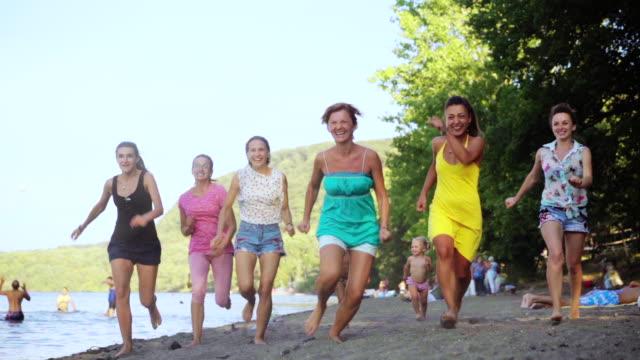 freunde, die spaß am strand entlang laufen. gruppe der glückliche mädchen springen und spaß haben, viel zeit in die beach-party. sommer-urlaub. slow-motion 100fps - spring break stock-videos und b-roll-filmmaterial