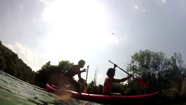 Friends having fun while paddling canoe video
