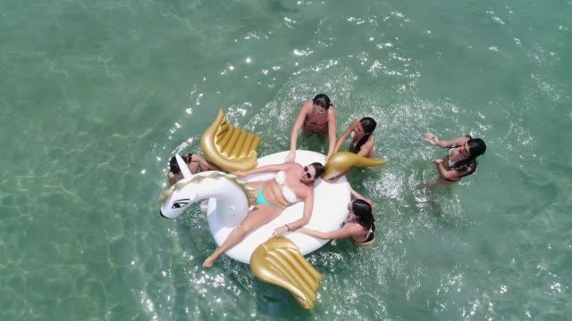 vídeos y material grabado en eventos de stock de amigos que se divierten con flotador inflable en la playa - vista aérea - unicornio