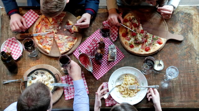 Friends having lunch in pizzeria and toasting with wine