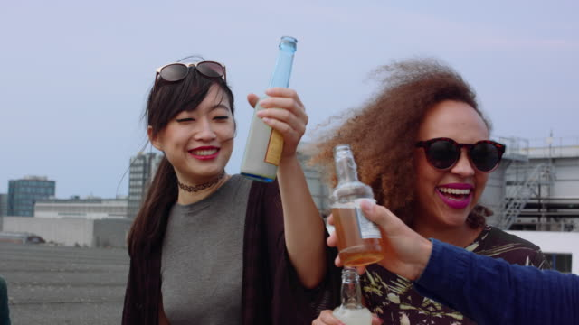 Friends having rooftop party Group of friends toasting drink at party. Young people hanging out on rooftop and having party. candid stock videos & royalty-free footage