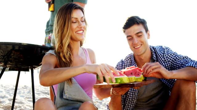 Friends having watermelon on the beach 4k - video