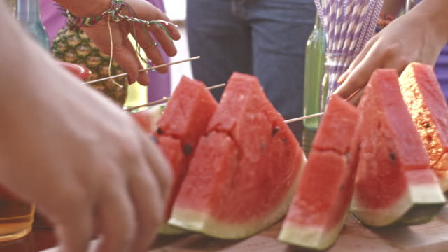 Friends having watermelon while on a party video