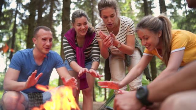 vídeos de stock e filmes b-roll de friends heating hands around campfire - 20 24 anos