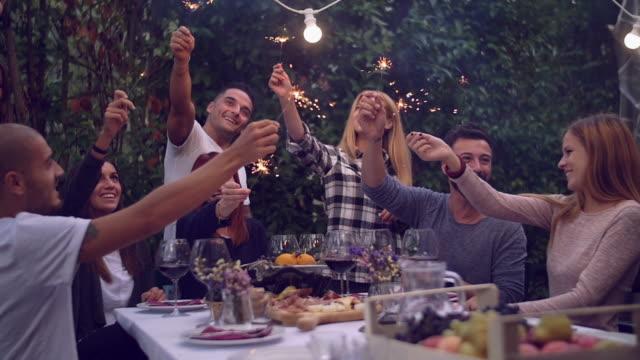 Amigos segurando lit estrelinhas em um jantar - vídeo