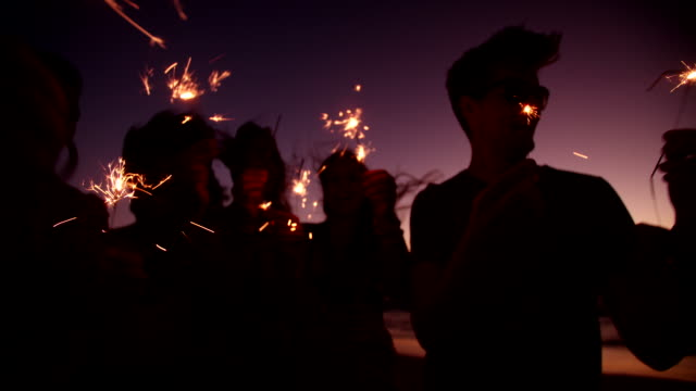 friends holding sparklers at a beachparty at twilight - new year 個影片檔及 b 捲影像
