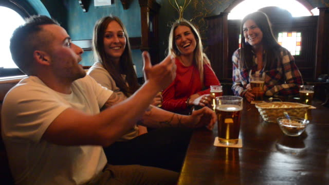 friends in a pub - sorriso aperto video stock e b–roll