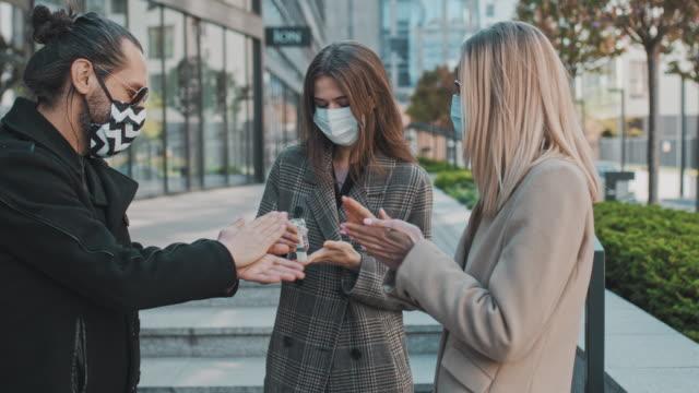 friends in face masks meeting in the city during coronavirus pandemic. sharing hand sanitizer - rozkładać filmów i materiałów b-roll