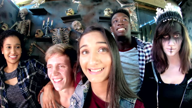 Friends in halloween haunted house, bones, evil princess A multi-ethnic group of four teenagers and young adults, two couples, exploring a halloween haunted house. They are in front of a wall covered with skeletons, looking uncomfortable. Standing with them is a scary looking evil princess or zombie. animal skeleton stock videos & royalty-free footage