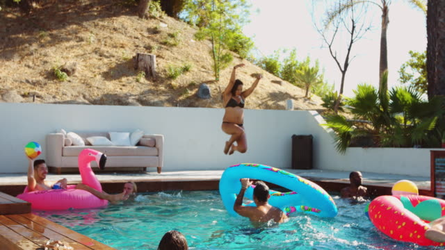 Friends Jumoing in and Playing with Pool Toys in Beautiful Outdoor Swimming Pool video