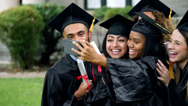 friends jump in to a self portrait of two female graduates - graduation stock videos and b-roll footage