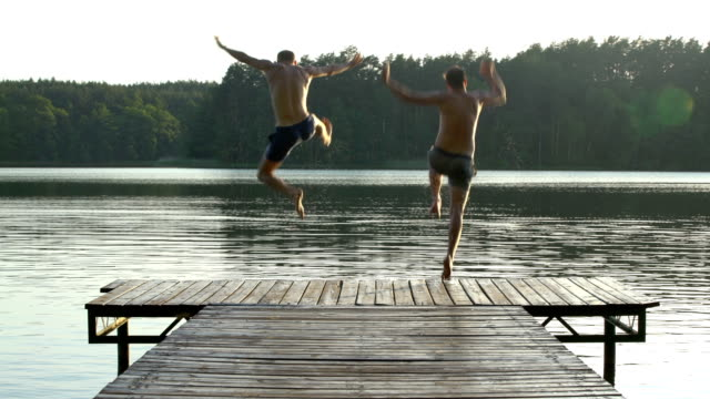 friends jumping into lake. summer activity - jezioro filmów i materiałów b-roll