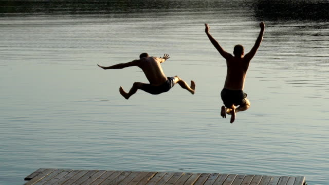 friends jumping into lake. summer activity - lakes stock videos and b-roll footage