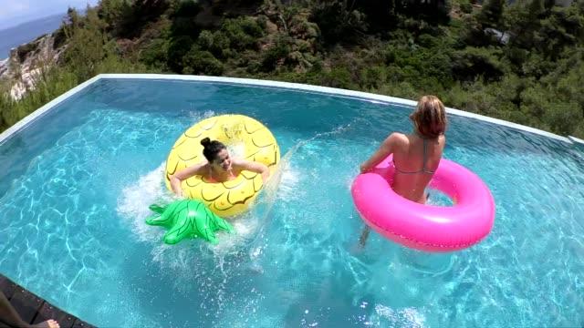vídeos de stock, filmes e b-roll de amigos de saltar para a piscina - inflável