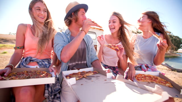 friends laughing and enjoying pizza on a summer day - pizza stock videos and b-roll footage