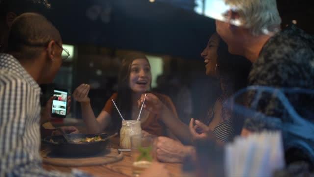 amici che ridono e si divertono con le notizie mobili al ristorante - happy hour video stock e b–roll