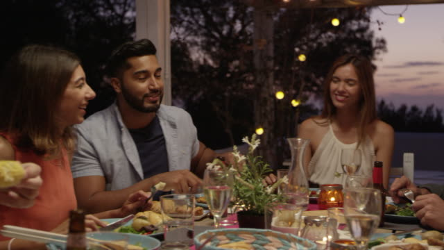 Friends laughing at a dinner party on a roof terrace, Ibiza, shot on R3D video