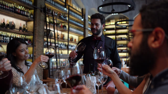 Friends learning about wine during a wine tasting following friendly sommelier