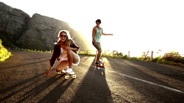 Friends longboard skating on road sunset video