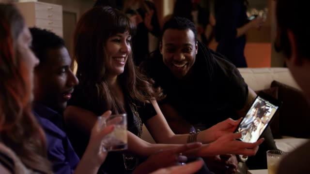vidéos et rushes de amis regardent les photos sur une tablette - soirées habillées