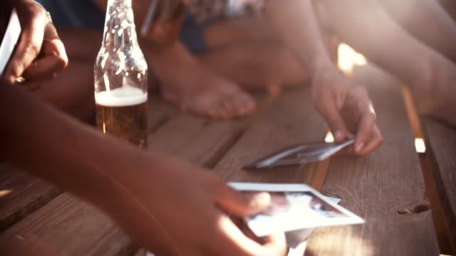 stockvideo's en b-roll-footage met friends looking at instant photographs of summer fun - polaroid