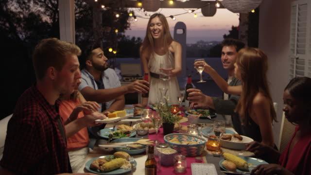 Amigos hacen un brindis durante la cena en una terraza, Ibiza, disparos a R3D - vídeo