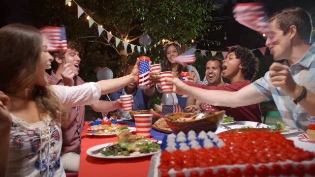 friends making a toast to celebrate 4th of july at party - 4 luglio video stock e b–roll
