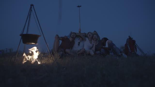 stockvideo's en b-roll-footage met 4k: vrienden maken selfie rond het kampvuur. - 25 29 jaar